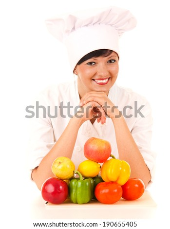female cook in uniform with fruit and vegetables, white background - stock photo