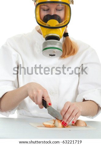 female cook in white uniform and gas mask cutting onion - stock photo