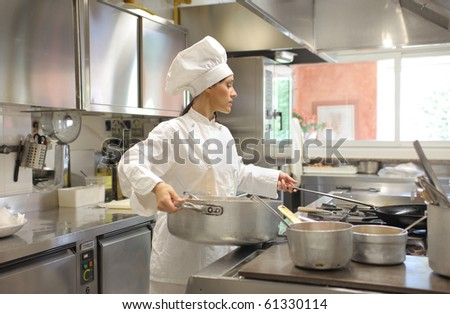 Female cook preparing food in a restaurant kitchen - stock photo