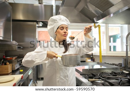 Female cook tasting some food in a restaurant kitchen