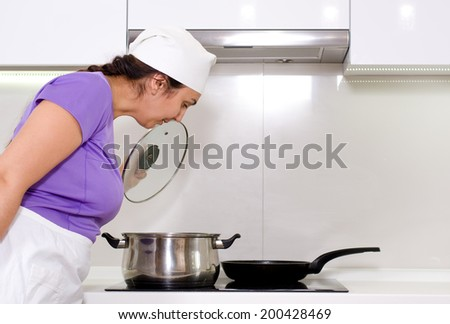 Female cook watching a pot boil on the stove in her white apron and chefs toque - stock photo