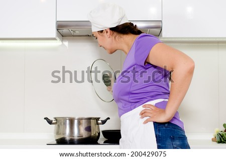 Female cook watching a pot boil on the stove in her white apron and chefs toque