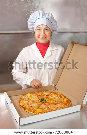 female cook with cooked pizza in box