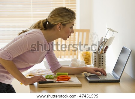 female cooking and looking up recipes on-line in kitchen