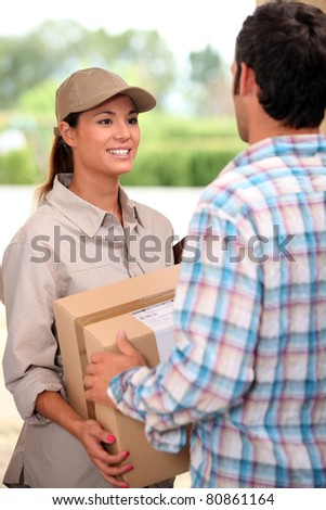 Female courier delivering package - stock photo