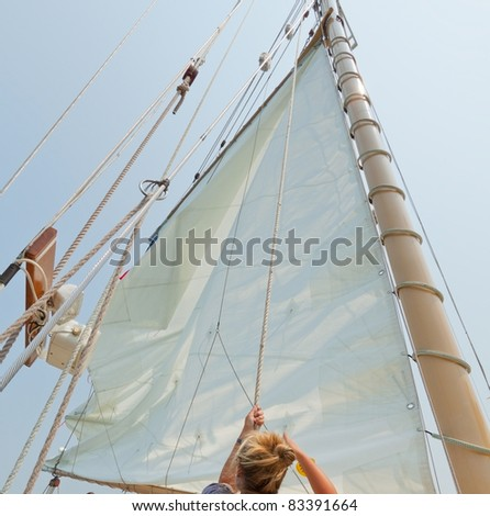 Female crew member raising sail on the private sail yacht. - stock photo
