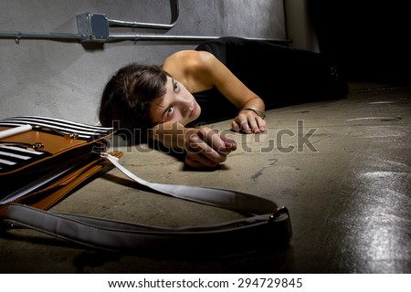 female crime victim laying on the street floor or passed out drunk.  she is in a street alley with her bag in the foreground.  she was either mugged or hungover. - stock photo
