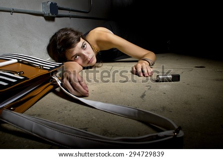 female crime victim laying on the street floor with a can of mace.  she failed to use the pepper spray for self defense and is laying injured on the street. - stock photo