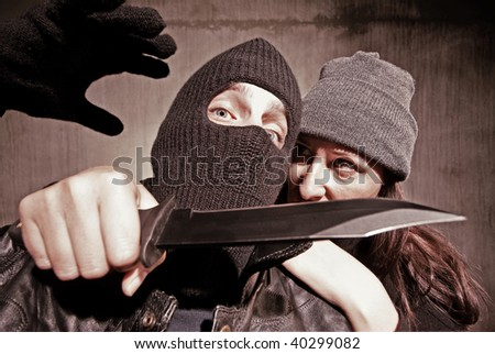 Female criminal with knife to the neck of her rival - stock photo