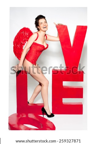 Female cupid in red corset with love word inscription - stock photo