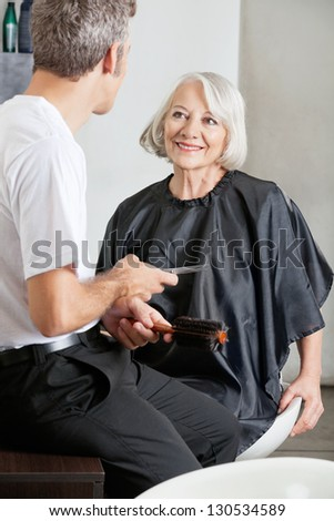 Female customer and hairstylist having conversation before haircut at salon