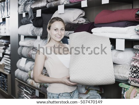 Female customer choosing blanket in bedding section in shop