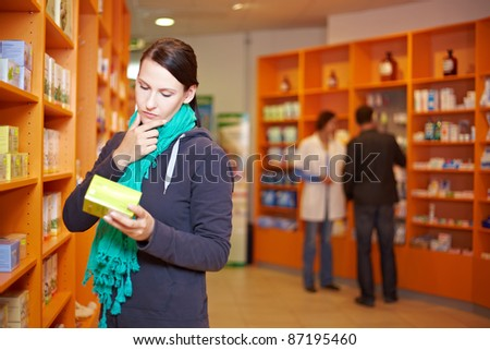 Female customer decides for a product in a pharmacy - stock photo
