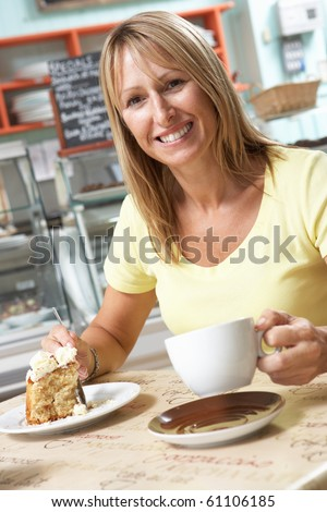 Female Customer Enjoying Slice Of Cake And Coffee In Cafe - stock photo