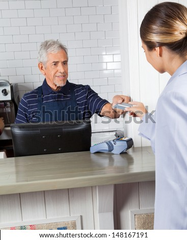 Female customer giving credit card to male cashier at counter in grocery store - stock photo