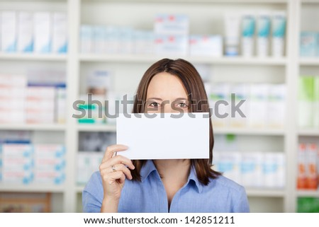 Female customer holding and showing a blank sign standing inside the pharmacy. - stock photo
