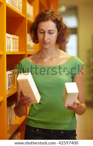 Female customer in pharmacy comparing two medications