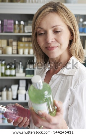 Female Customer In Shop Choosing Beauty Products - stock photo