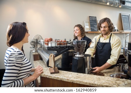Female customer looking at baristas making coffee in cafeteria