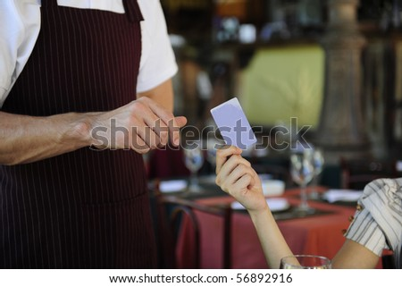 female customer paying with credit card at the restaurant - stock photo