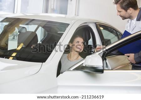 Female customer receiving car key from mechanic in automobile repair shop - stock photo