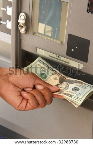 Female customer retrieving money from ATM - stock photo