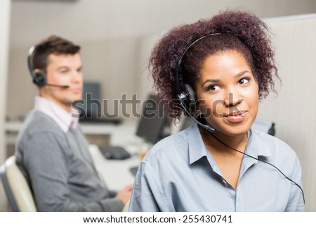 Female customer service representative wearing headset with male colleague in background at office - stock photo