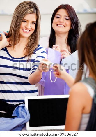 Female customer shopping and paying by credit or debit card at a store
