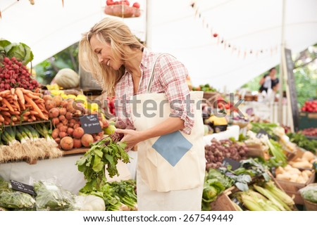 Female Customer Shopping At Farmers Market Stall - stock photo