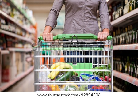 Female customer shopping at supermarket with trolley