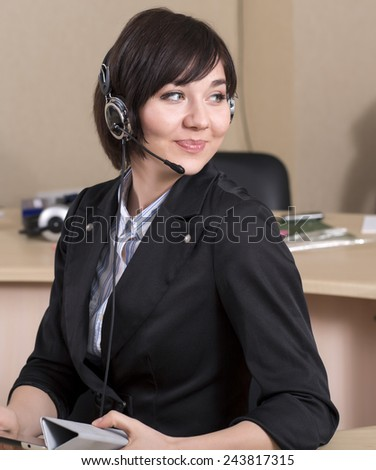 Female customer support officer sitting half-turned. Portrait of smiling cheerful customer support phone operator in headset  - stock photo