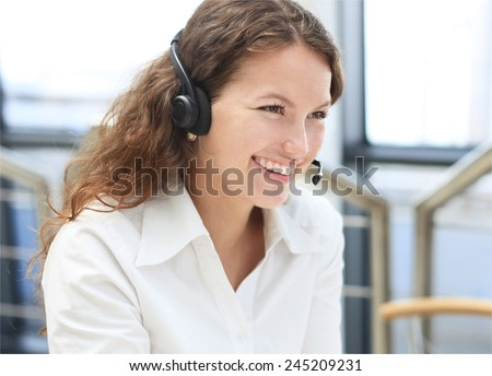 Female customer support operator with headset and smiling  - stock photo