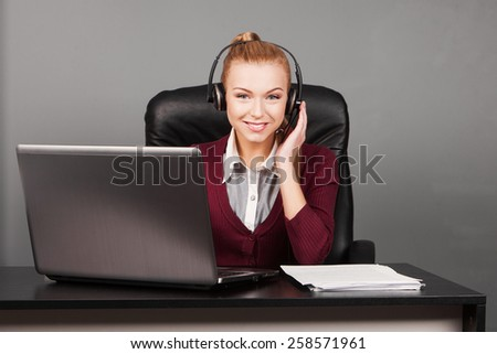 Female customer support operator with headset and smiling. Call center woman