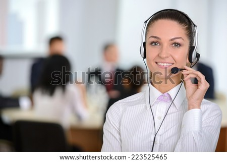 Female customer support operator with headset and smiling, people group in background at modern bright office indoors