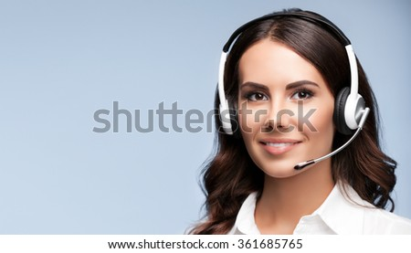 Female customer support phone operator in headset, against grey background, with copyspace area for slogan or text message