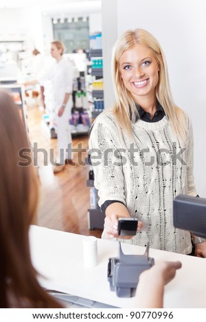 Female customer using cell phone to pay for goods - stock photo