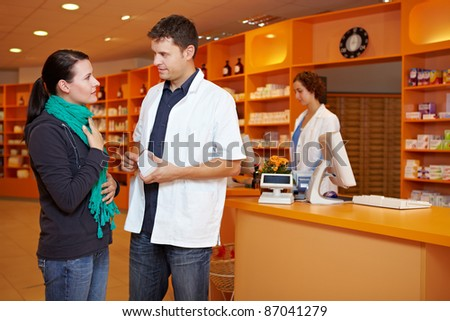 Female customer with cold gets advice from pharmacist in pharmacy - stock photo