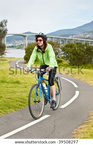 Female cyclist on s bend of cycle path