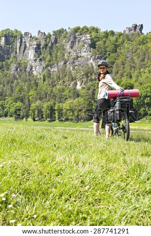 Female cyclist traveling on a bicycle with a load. The woman is standing on a hill and looking at the camera. - stock photo