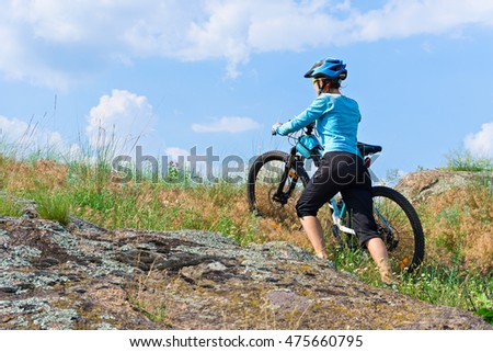 Female cyclist with her mountain bike climbing up a rock on foot.