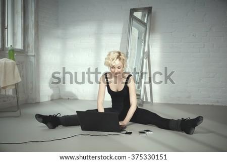Female dancer sitting on floor using laptop computer. - stock photo