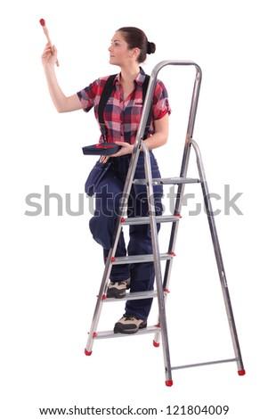 Female decorator climbing a ladder - stock photo