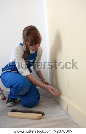Female decorator hanging wallpaper