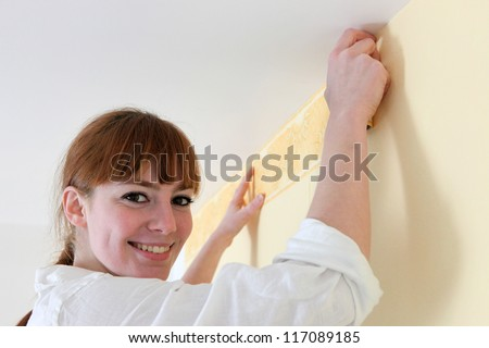 Female decorator hanging wallpaper border - stock photo