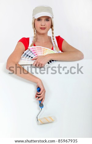 Female decorator with a color chart and roller - stock photo