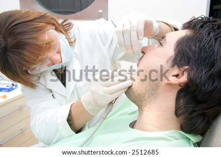 Female dentist examining a male patient - stock photo