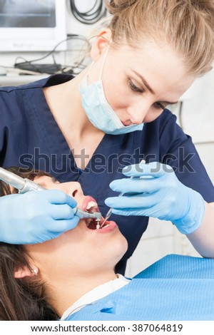 Female dentist examining a woman patient at clinic using dental tools as orthodontic equipment concept - stock photo