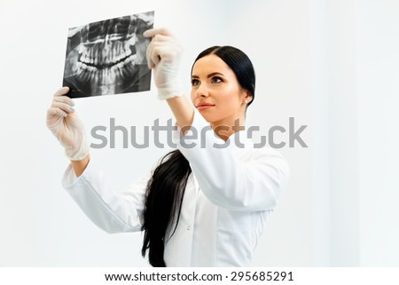 Female Dentist Looking at Dental Xray in Clinic - stock photo