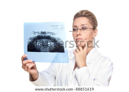 Female dentist looking at the teeth x-ray - stock photo
