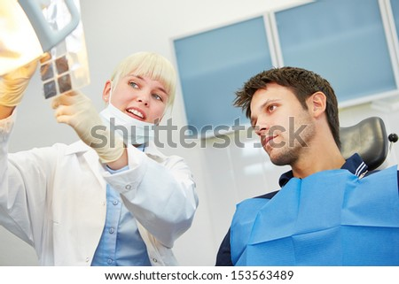 Female dentist showing patient caries on x-ray image prior to dental treatment - stock photo